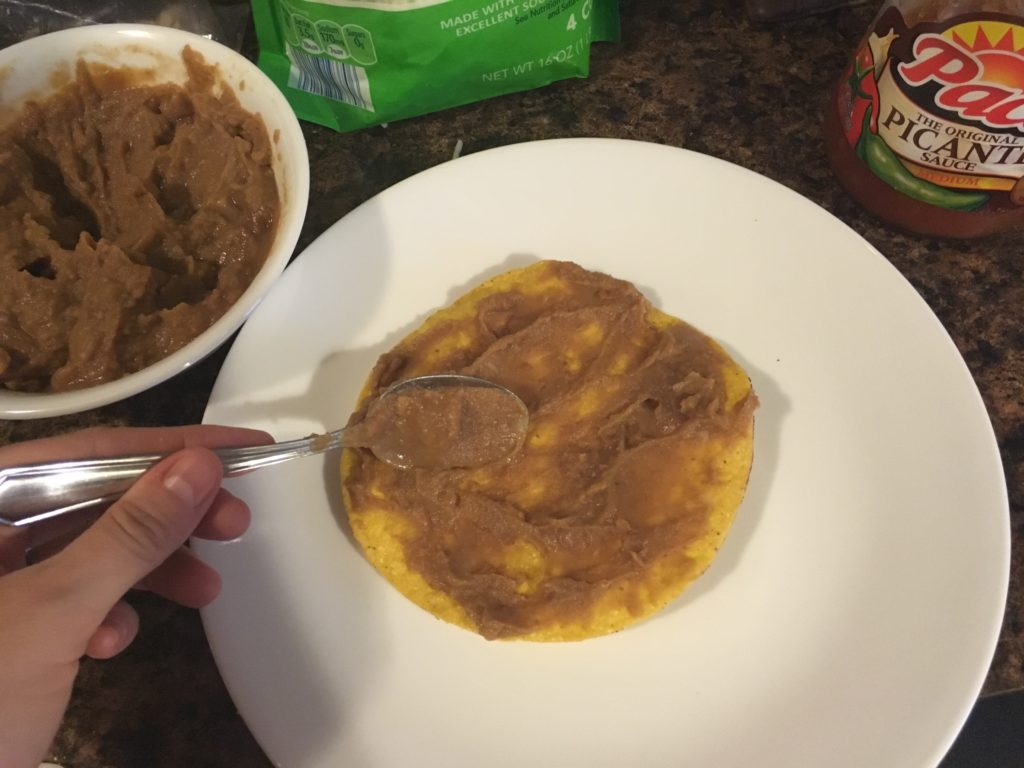 spreading refried beans on a tostada