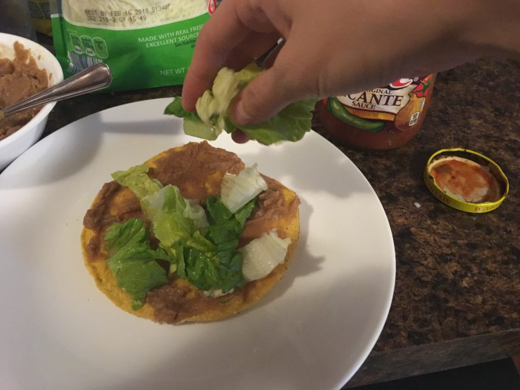 adding lettuce to a tostada